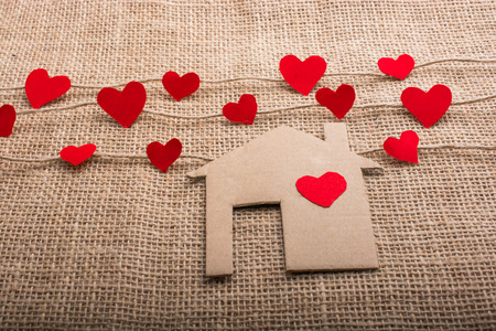 Heart shaped icons and paper house on linen threads 스톡 콘텐츠