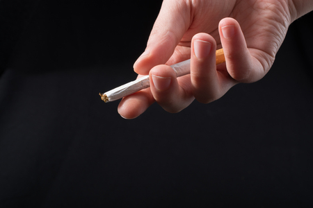 Hand is giving out cigarette on a black background