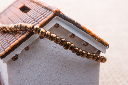 Beads wrapped around  a model house  on a brown background