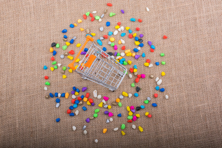 Little trolley amid Colorful pebbles on canvas background Stock Photo
