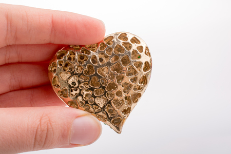 Heart shaped gold color metal object in hand Stock Photo