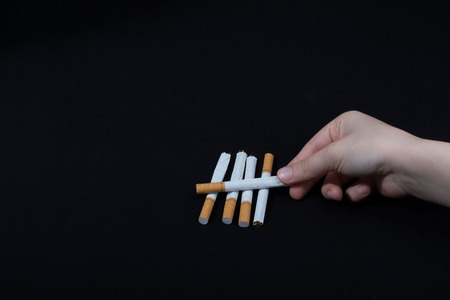 Hand is holding crossed cigarettes on black background Stock Photo