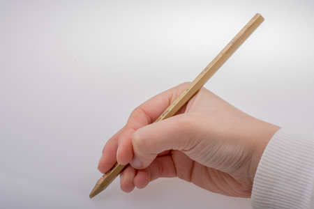 Hand holding a gold color pencil on a white background Stock Photo