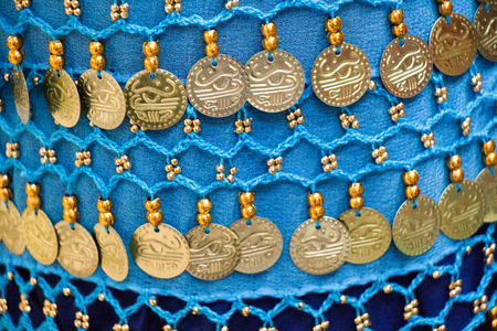 Plenty of fake gold coins are on the scarf edges