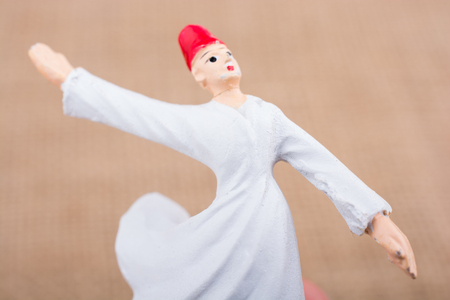 Hand holding a white color Sufi Dervish figurine in hand
