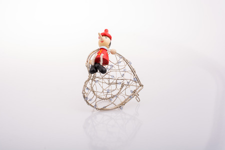 Wooden Pinocchio doll sitting on  a heart shaped cage