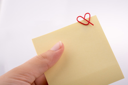Hand holding a notepaper  heart shaped clip on a white background