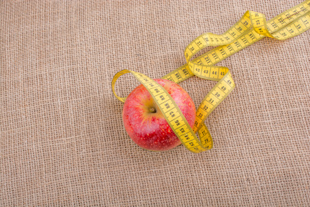 Health and diet concept with apple with a measurement  tape