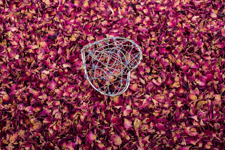 Heart shaped cage placed on dry rose petals Stock Photo