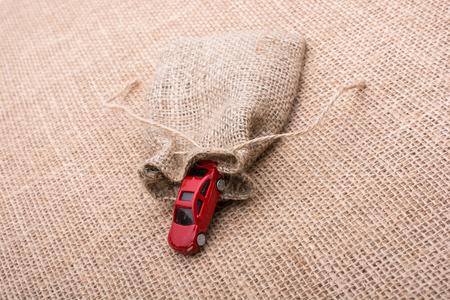 Red toy car coming out of a linen sack on a linen canvas Stock Photo