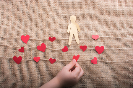 Paper man and heart icons on linen threads on canvas