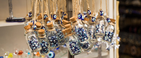 Little transparent glass bottle filled with blue evil eye beads
