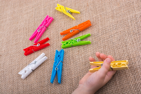 Color clothespin in hand on a linen canvas background