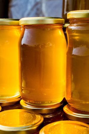 Glass jar of full of fresh honey with lid