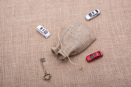 Key and toy cars around a sack on a linen canvas