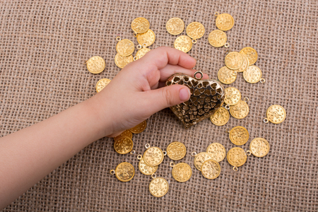 Fake gold coins around gold color heart in hand