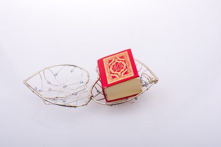 The Holy Quran in mini size in a heart shaped cage
