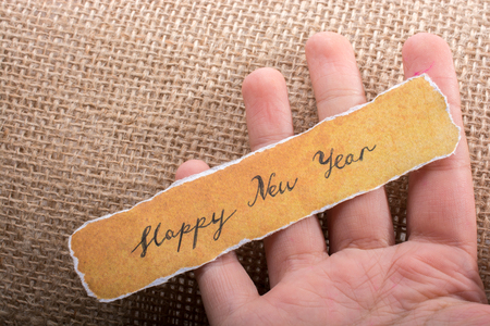Happy new year written on a torn yellow paper in hand Stock Photo