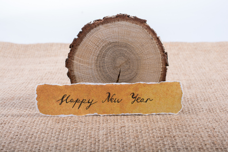 Happy new year written torn  paper  on a piece of log