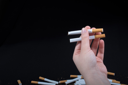 Hand is holding cigarettes on a black background Stock Photo