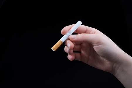 Hand is holding cigarette on a black background Stock Photo