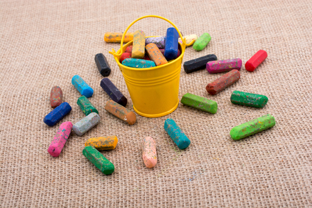 Crayons of various color in a bucket on a canvas