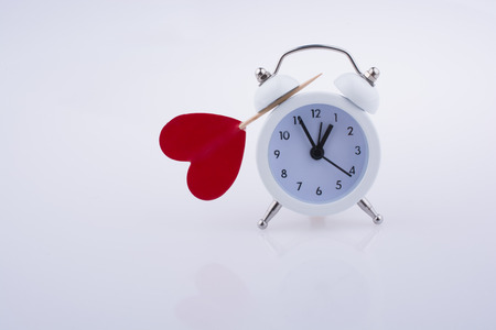 Little red color heart shape and white color alarm clock Stock Photo