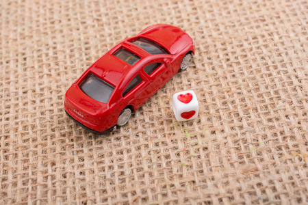 Love cube on a red toy car on a linen canvas Stock Photo