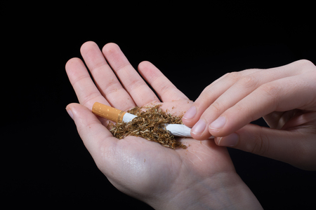 Hand is breaking a cigarette on a black background