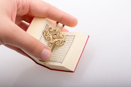 Hand holding Key and Islamic Holy Book Quran in mini size