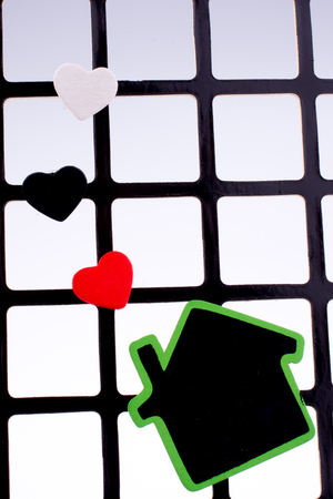 Green house on a grill with a few hearts Imagens