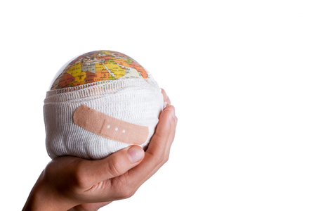 Child holding a globe with plaster in his hand on a white background Banque d'images - 103314040