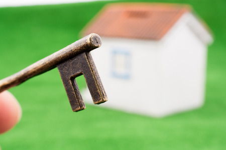 Hand holding a House key near a house model on green grass