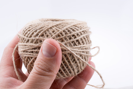 Spool of linen thread in hand on white background