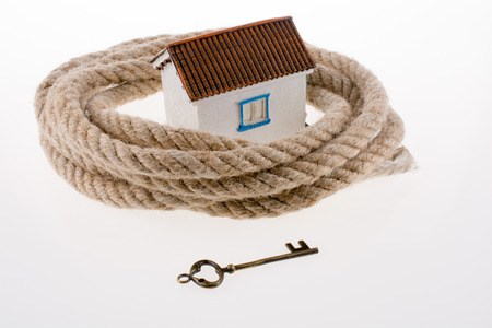 key and house surrounded by rope on a white background