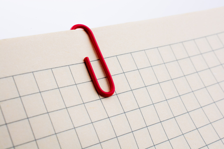 Colored paper clip on a checked notebook  page