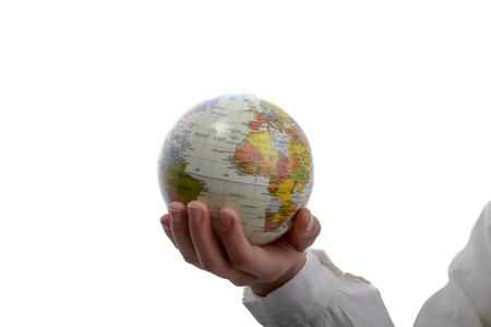 Child holding a small globe in hand on white background Foto de archivo