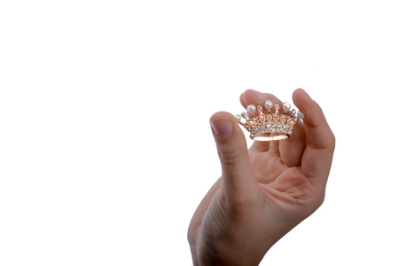 Golden color crown with pearls in hand on a white backgound Stock Photo - 102005830