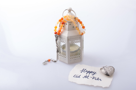 the word EID EL FITR   on torn paper beside a lantern and prying beads Stock Photo