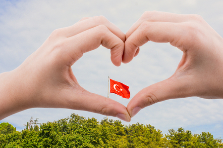 Turkish flag seen behind a heart shaped hand