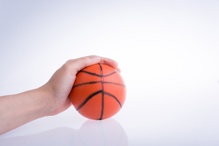 Hand holding an orange basketball model on a white background 写真素材