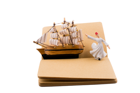 Sufi Dervish and a ship on a notebook on white background Stock Photo