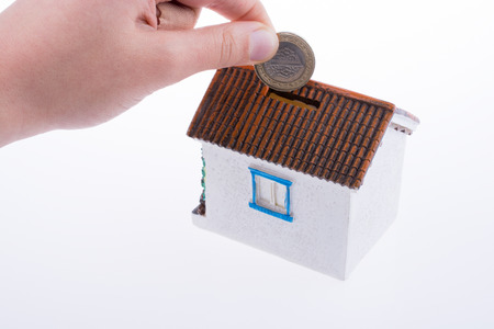 Hand dropping coin into the moneybox in the shape of a model house Banque d'images
