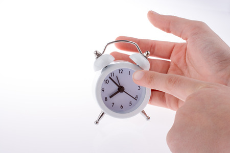 Alarm clock in hand on a white background Stock Photo