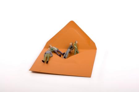 Figurine men out of an envelope on white background Banco de Imagens