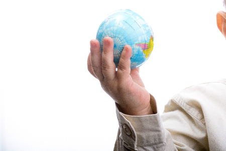 Baby holding a small globe in hand on white background Foto de archivo