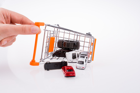 Cars near a shopping cart on white background