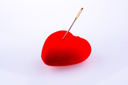 Hand pointing a needle on a heart