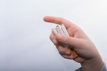Hand is holding bundle of cigarettes on white background