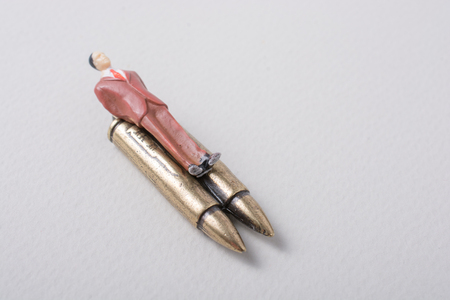 Man figurine tied to a  Bullet as anti-war photography